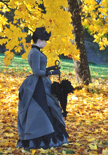 Women's Victorian day dress from the 1880s with bustle skirt, hat, parasol/umbrella. Women's victorian costumes and clothing