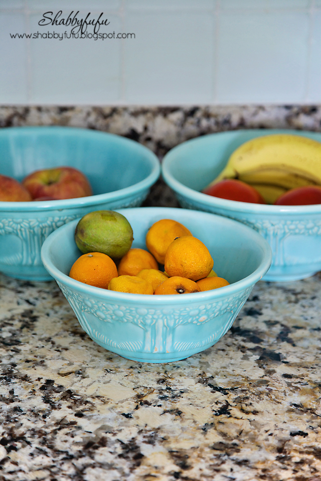 Adding pops of color to a room - light blue pottery contrasts with lemons, limes, and oranges