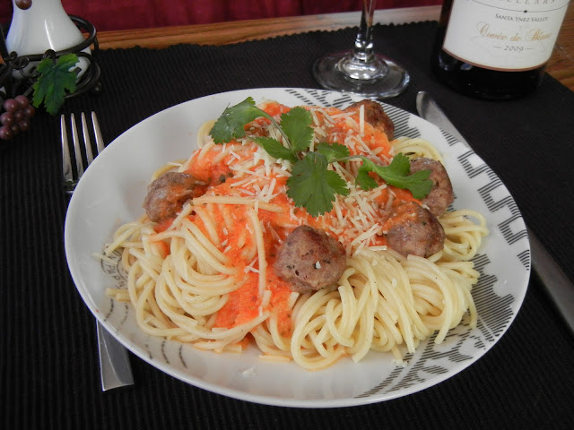 pasta with meatballs and sauce on top with parsley as granish