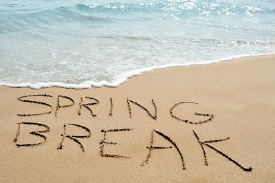 "photo of a beach shoreline, etched into the sand is ""Spring Break."""