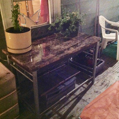 Discarded desk re-purposed as outdoor garden work table for Urban Container Gardening
