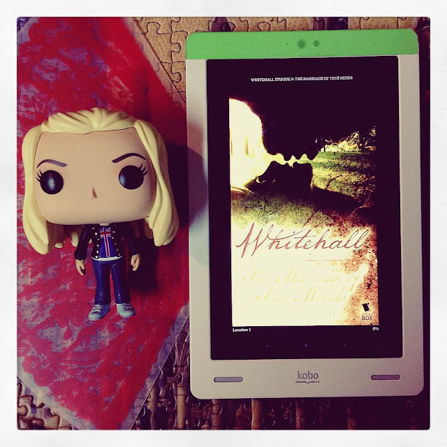 A large-headed Funko Pop of Rose from Doctor Who lies next to a white Kobo with Whitell Episode Nine's cover on its screen. The cover depicts two silhouetted faces, one hovering above the other. They look set to kiss upside down.