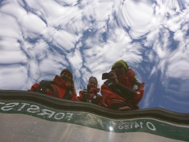 Kolme henkeä veneessä ja pilvipoutainen taivas heijastuvat tyynen meren pinnalta