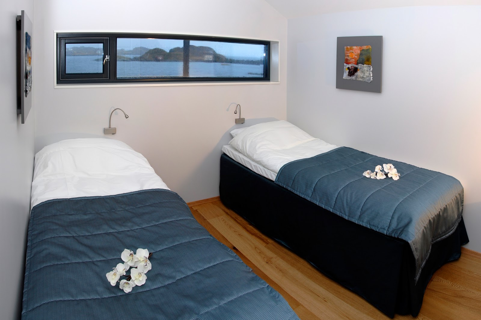 Two single beds are located in the first of two of bedrooms (my recommendation) in each of the villas. Notice the spectacular view outside the windows. This photo only: © Hamn I Senja. Unauthorized use is prohibited.
