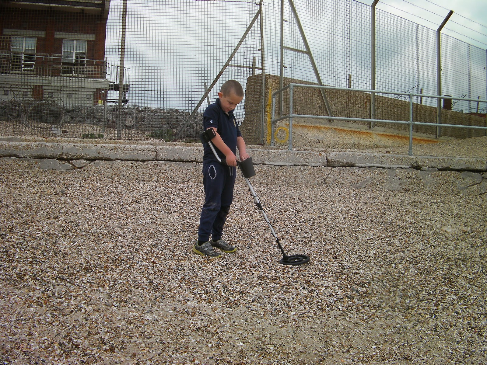 metal detectorist on shingle beach eastney in front of derelict cold war listening station