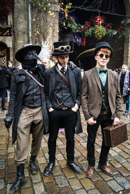 A group of fashionably dressed hipster men in Steampunk/neo-victorian clothing. One is dressed as a plague doctor with mask.