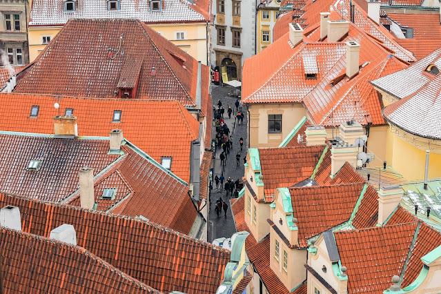 Foto de uma rua pequena com os telhados das casas visíveis onde pessoas caminhas nas ruas, ilustrando texto sobre propriedade aparente e posse imobiliária.
