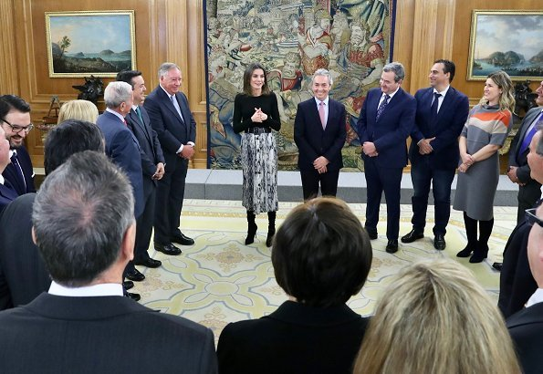 Queen Letizia wore Zara snakeskin print belted skirt, and Hugo Boss top, and Magrit suede boots at Vogue Spain