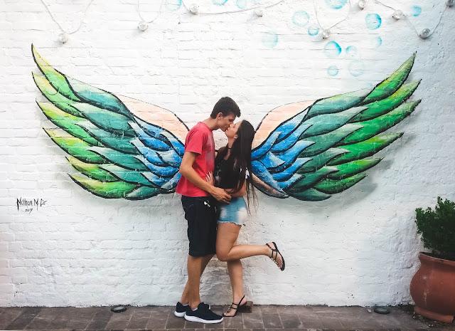 Casal se beijando em frente a asas desenhadas na parede