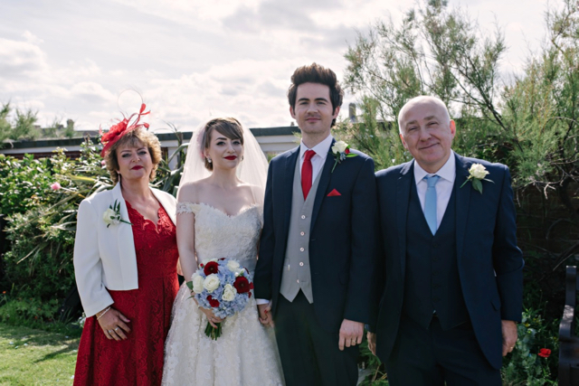 Bride and groom with mother and father of bride at vintage seaside wedding