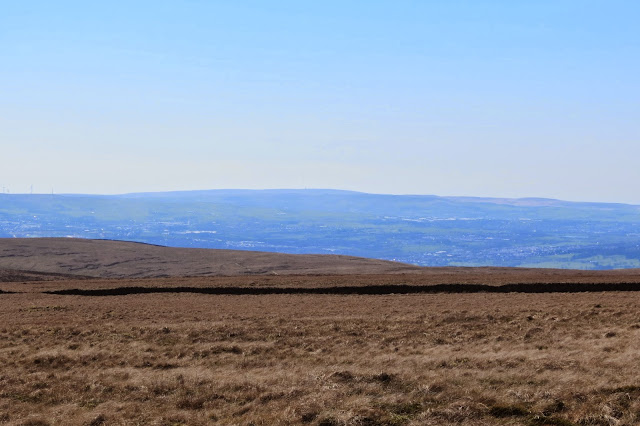 A view across the expanse of Pendle Hill to the broad outline of Winter Hill on the horizon, with its TV transmitter just visible in the haze.