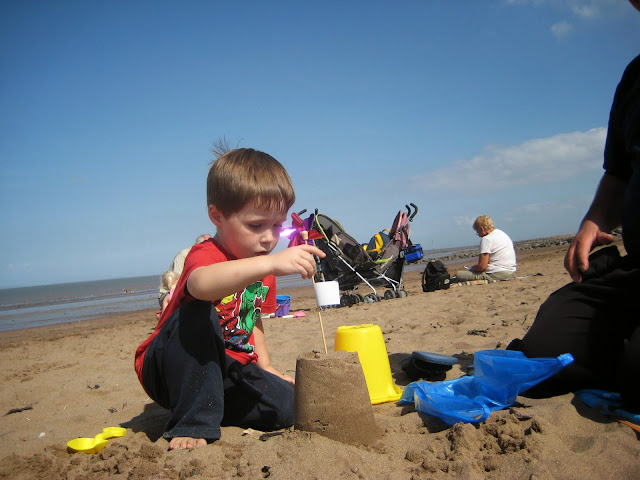 Child building a sandcastle on the beach.