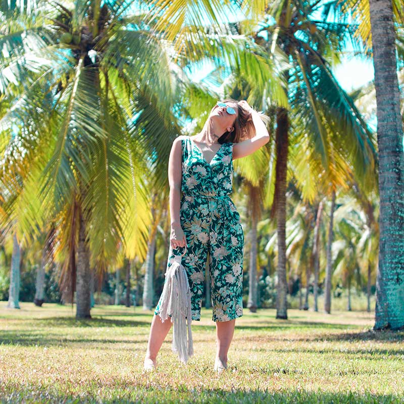 girl wearing floral culotte jumpsuit with tassel bag in field of palm trees