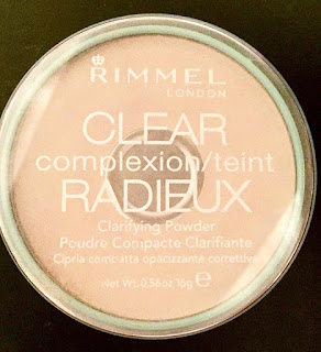 A circular pot filled with a beige clear translucent powder with a clear plastic lid which says Rimmel Clear Compexion on the top on a bright background.