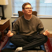 David Borden sitting in a very bad Buddha pose.
