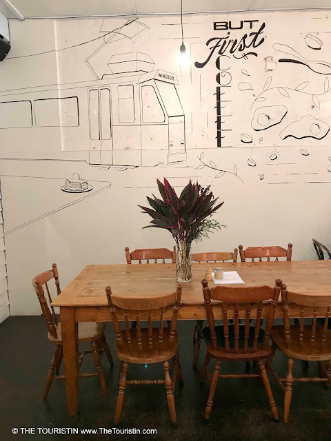 Wooden community table in front of a black and white wall mural