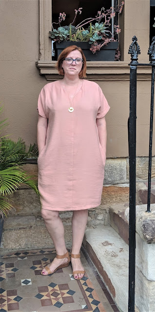 Wearing the cocoon dress with hands in pockets