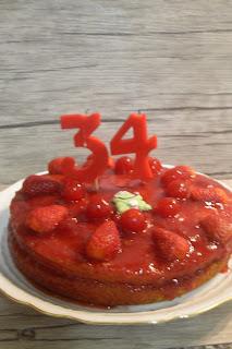 Pastel de cumpleaños de mermelada de fresas con fresas y cerezas sin lactosa.