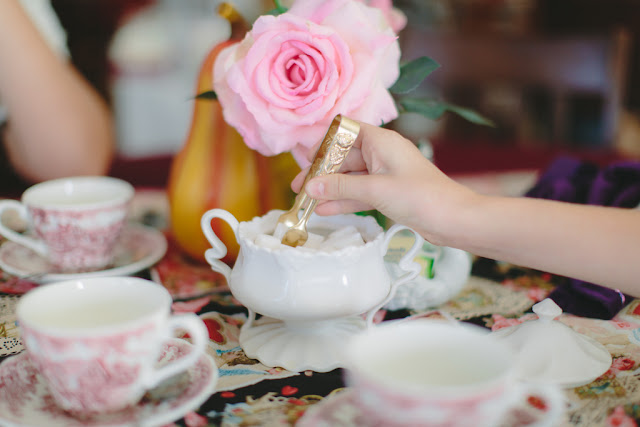 Table setting with pink rose, sugar cubes and tea cups