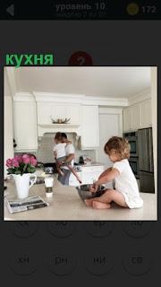 на кухне на столе сидит ребенок с кастрюлей