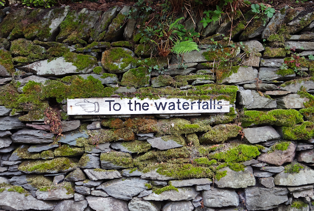 sign pointing 'to the waterfalls' on an old stone wall