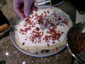 Adding bacon on top of the thin crust pizza dough or tartes flambee