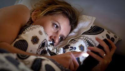 Gulinti lovoje mergina žiūri į išmanųjį telefoną