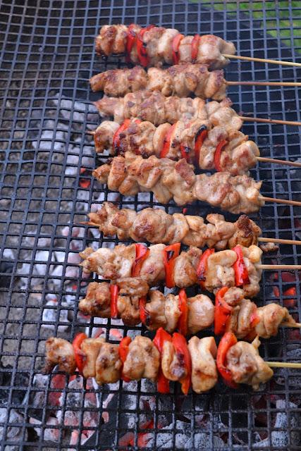 9 sateprikkers met stukjes kip en paprika liggen op het rooster van een grote barbecue