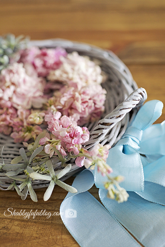 Close-up detail on my floral peony wreath with light pink peonies in a soft grey wicker basket.