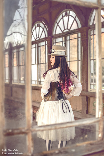 Women's steampunk fashion: white dress/skirt/blouse, brown leather corset, gray top hat, goggles.