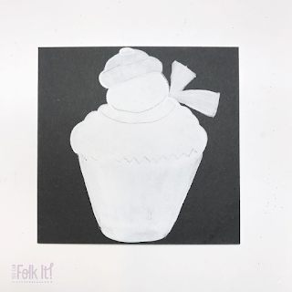White silhouette of a snowman topped cupcake with pencil lines marking out the details