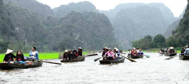 Tourists from all over the world enjoy the beauty of Tam Coc river, Vietnam