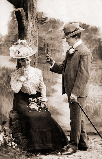 Couple poses for a photo. c. 1900. Woman with a lap of flowers. Frighten the Horses. marchmatron.com