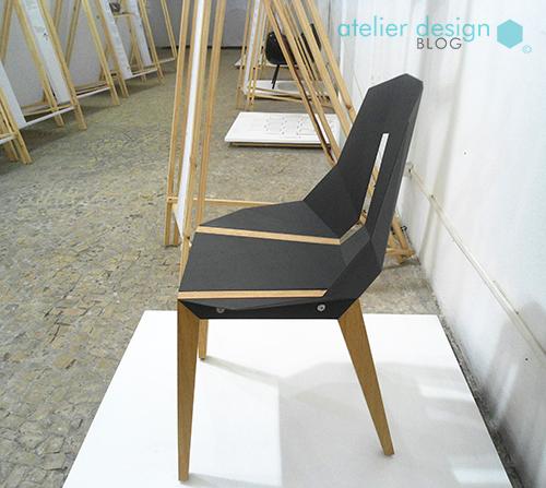 imagem de uma cadeira feita com placa de alumínio e pés de madeira. Sendo que seu formato tem referências do origami