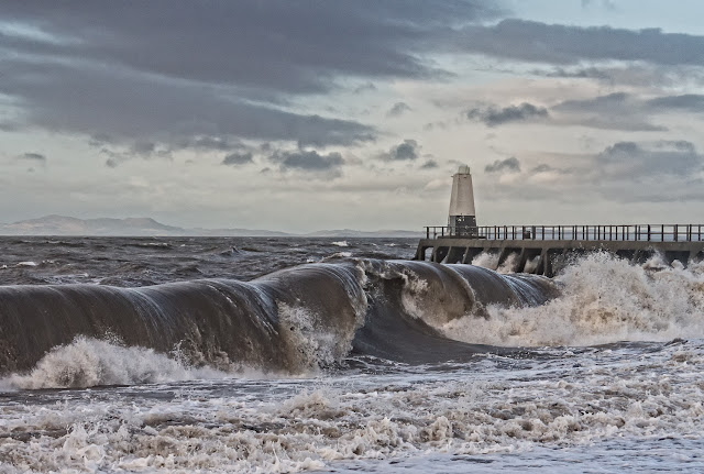 Photo of a powerful wave rolling onto the shore at Maryport