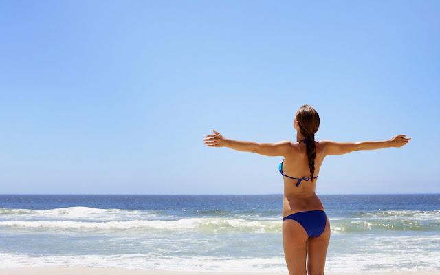 Vrouw in bikini bij de zee