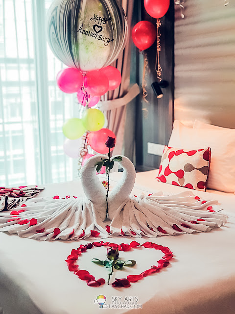 Couple swans on the bed with a huge Happy Anniversary balloon floating in the air - Ramada KLCC
