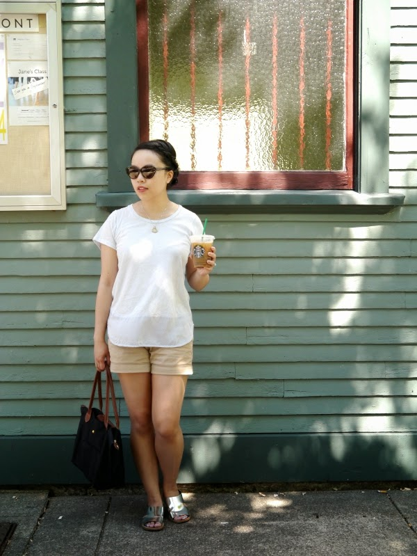 Simple summer chic in a silk/cotton powder blue tee, khaki shorts, silver sandals, and cat-eye sunnies