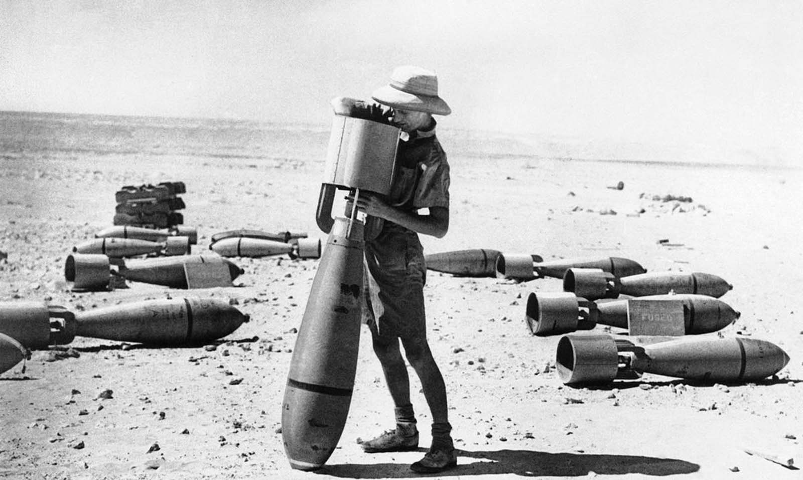 This armorer of the R.A.F.'s middle east command prepares a bomb for its mission against the Italian forces campaigning in Africa. This big bomb is not yet fused, but when it is it will be ready for its deadly work. Photo taken on October 24, 1940.