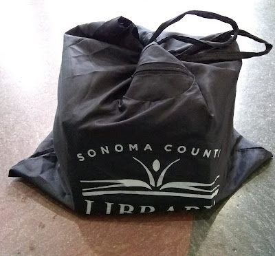 Black bag, filled, and tied shut at top. White lettering on front of bag reads, 'Sonoma County Library' and displays the library logo, a small human figure raising its arms behind an open book.
