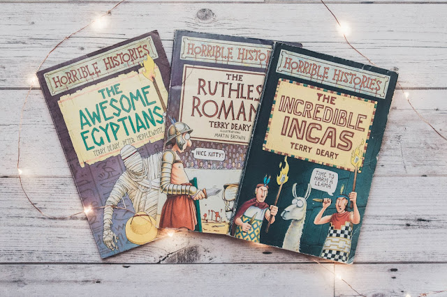 the Horrible Histories books surrounded by fairylights