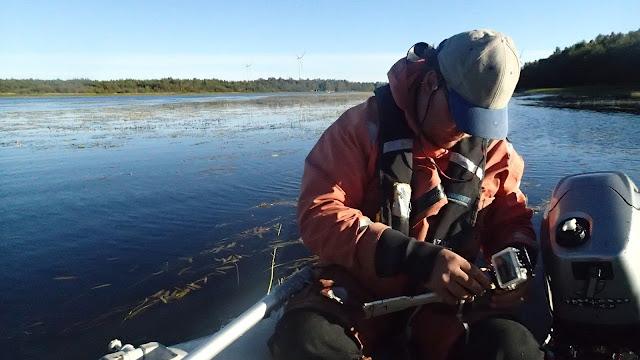Pelastautumispukuinen henkilö säätää Gopro-kameraa ja ajaa kumivenettä
