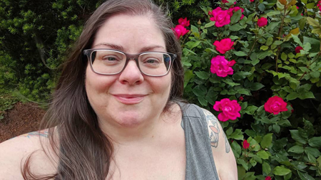 image of me from the shoulders up standing in my garden in front of a rose bush with large pink blooms, with my hair down and blowing in the breeze, wearing grey-framed glasses and a grey tank top