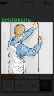 Мужчина в рабочей одежде делает отвесом вертикаль на стене