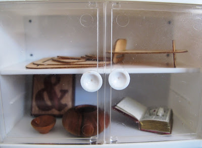 Modern dolls' house miniature glass-fronted display cupboard containing a modern wooden tray, an ampersand tile, two pieces of wood turning, and a book safe.
