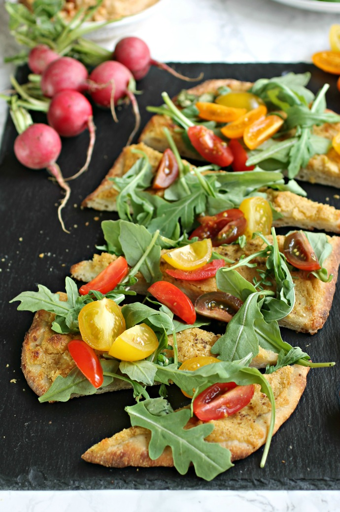 Recipe for an appetizer pizza with hummus and salad greens.