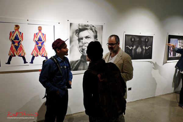 Talking to gallery patrons, Frank Ockenfels 3 at Black Eye Gallery. Photography by Kent Johnson for Street Fashion Sydney.