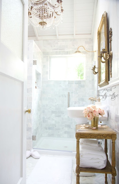 Marble bathroom with gold stand and crystal chandelier