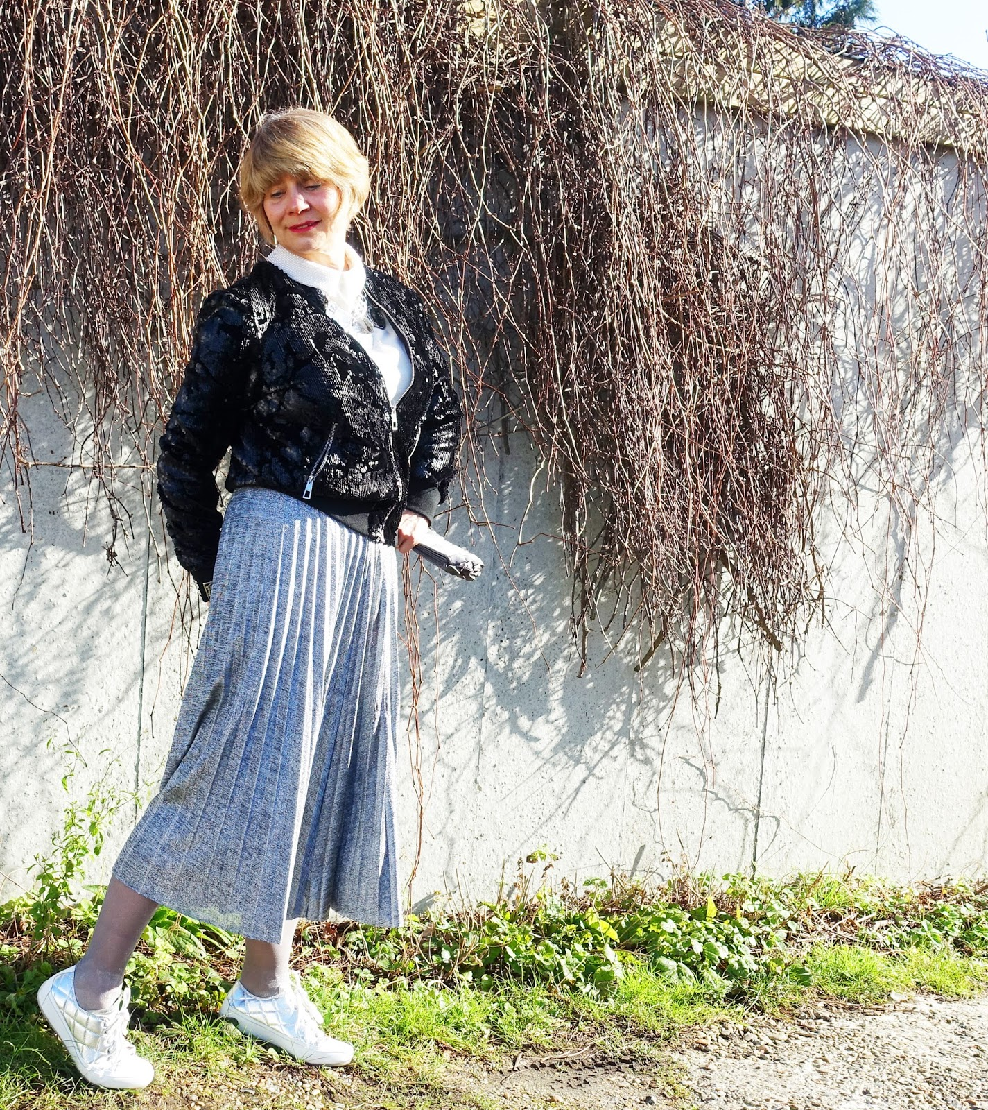 Gail Hanlon from mid life fashion blog Is This Mutton in silver pleated skirt, black sequinned bomber jacket, silver Vionic shoes