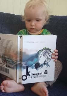 Lilla Eila tittar i boken Klimatet och Omställningen